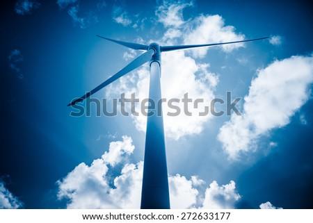 wind generators aganist the blue sky, blue toned. - stock photo