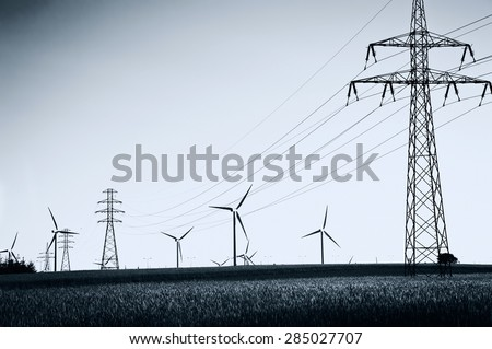 Wind Generators and power lines. Ecology and alternative energy. Dark picture. - stock photo