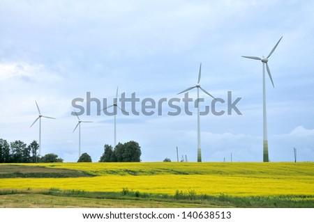 Wind Generators in rapeseed field - stock photo