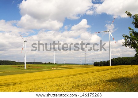 Wind mill generators on a yellow field with blue sky and clouds - stock photo