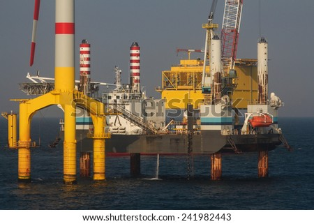 wind mill installation process in the north sea - stock photo