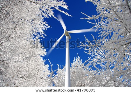 wind mills power generators against winter forest - stock photo