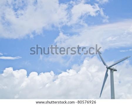 Wind power generator in blue sky - stock photo