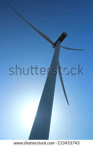 Wind power station - wind turbine as alternative energy source against clear blue sky with the sun as a source of backlight - stock photo