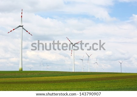 Wind power turbine spins over green landscape - stock photo