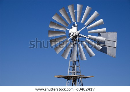Wind pump against a blue sky - stock photo