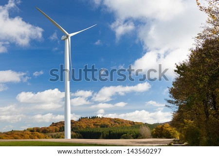 Wind turbine against blue sky and fall forest - stock photo