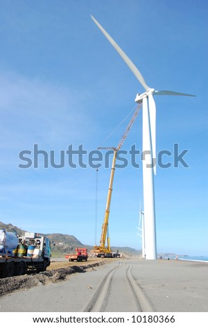 wind turbine and crane under maintenance - stock photo