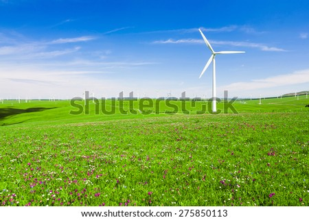 wind turbine and flower meadow under blue sky - stock photo