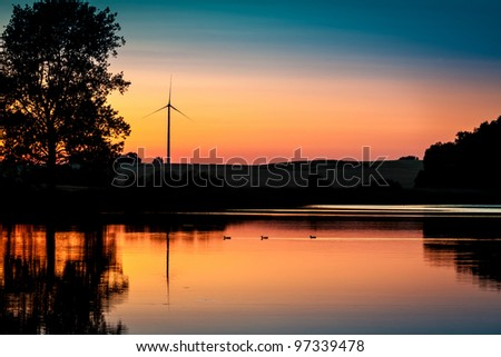 Wind Turbine and sunset at lake in summer - stock photo