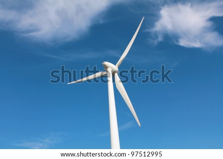 Wind turbine between clouds - stock photo