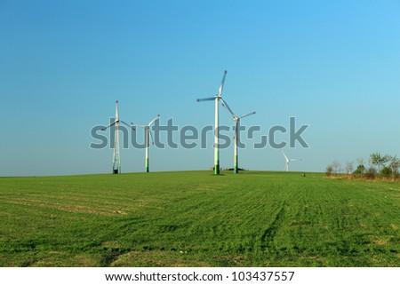 Wind turbine farm in the field - a renewable energy source - stock photo