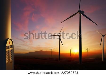 Wind Turbine farm with moody sunset (focused on nearest turbine on right) - stock photo