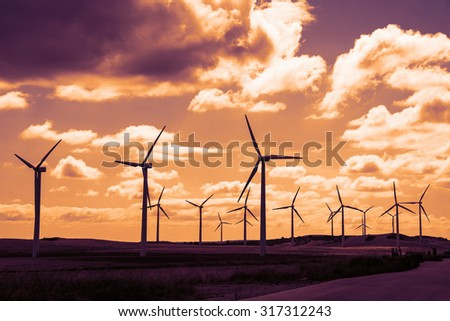 Wind turbine field at sunset, dramatic sky - stock photo