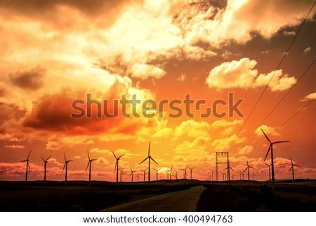 Wind turbine field at sunset, dramatic sky - stock photo