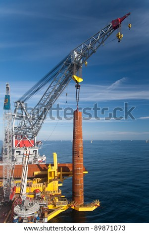 Wind Turbine foundation installation by a large crane vessel in the North Sea, off the Norfolk coast - stock photo