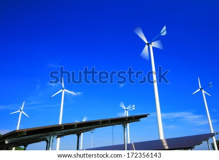 Wind turbine generator electricity and solar energy panels with blue sky. - stock photo