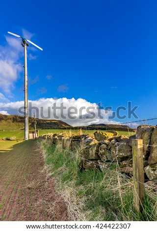 Wind turbine in a farmers field next to a stone wall - stock photo