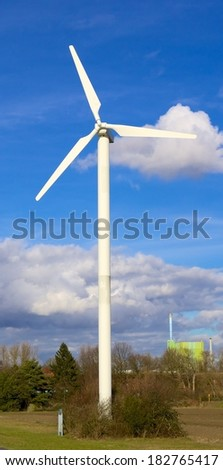 Wind turbine in front of a cloudy spring sky - stock photo