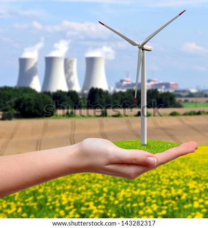Wind turbine in hand.In the background nuclear power plant - stock photo