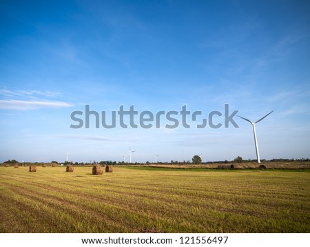 Wind turbine in hay field with blue sky in the background. - stock photo