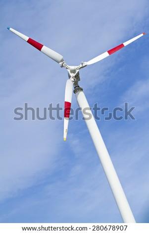 Wind turbine in on blue sky. - stock photo