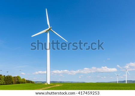 wind turbine of a small wind farm on a green field on a sunny day - stock photo