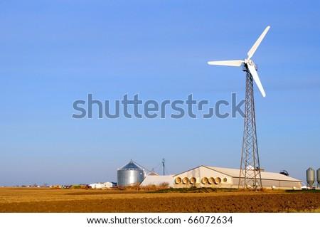 Wind turbine on a hog farm in Iowa - stock photo