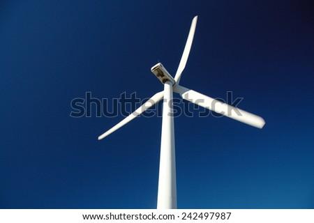 Wind turbine on blue background. Renewable energy source - stock photo