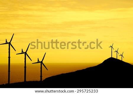 wind turbine on sunset sky with sea background - stock photo
