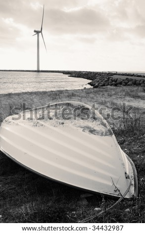 wind turbine or modern windmill by water with boat in foreground. Beach with ship and power generator creating renewable energy - stock photo
