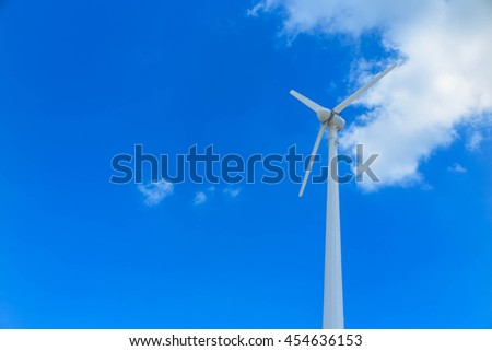 Wind turbine or windmill generating electricity on blue sky background - stock photo