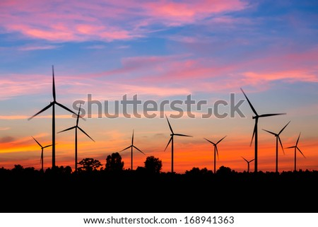 Wind turbine power generator at twilight - stock photo