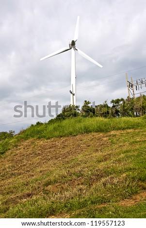Wind turbine producing alternative energy with a cloudy sky - stock photo