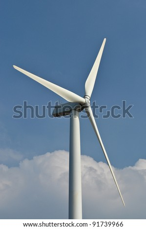 Wind turbine propeller blades against blue sky - stock photo