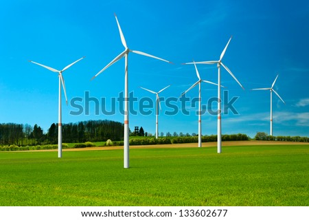 Wind turbine renewable energy source, summer landscape with clear blue sky and green field - stock photo