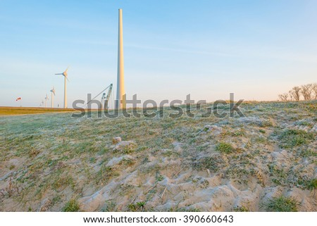 Wind turbine under construction along a dike - stock photo