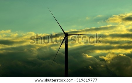 Wind turbine with clouds background, color effects - stock photo