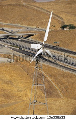 Wind turbine with freeway in background - stock photo