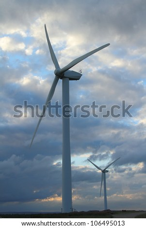 wind turbines against cloudy sky - stock photo
