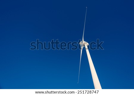 Wind turbines against dark blue sky. - stock photo