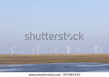 wind turbines and blue sky above Eempolder in the Netherlands with birds in meadow area - stock photo