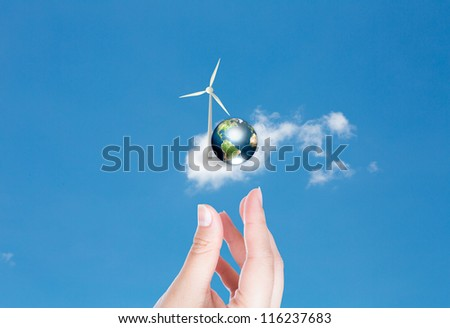 Wind turbines and earth with hand over blue sky (Elements of this image furnished by NASA) - stock photo