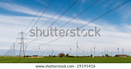 Wind turbines and Electricity Pylons in in a green field in East Sussex, England - stock photo