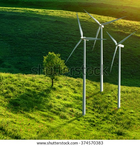 Wind turbines and tree on green meadow in summer. Eco energy concept. - stock photo