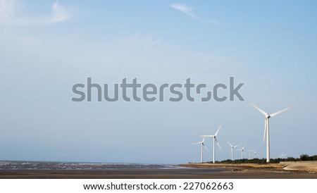 Wind turbines at seaside against blue sky - stock photo