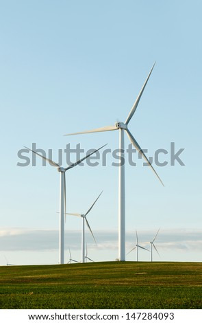 Wind turbines constructed in a farm field - stock photo