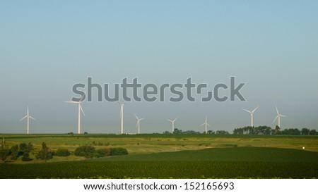Wind turbines farm at sunrise in Iowa. - stock photo