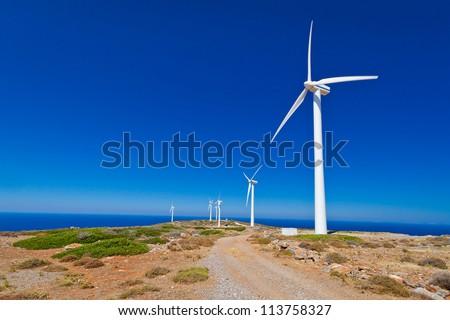 Wind turbines field over blue sky on Crete, Greece - stock photo