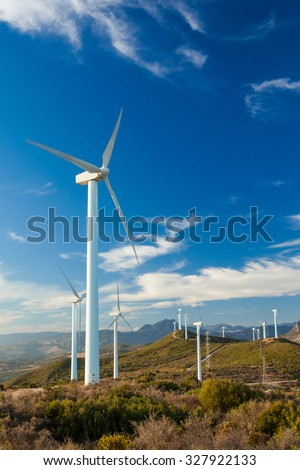 Wind Turbines generating electricity on a remote hillside in Southern Europe. Bright blue sky background with few white clouds. Portrait Format - stock photo